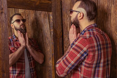 Stylish man with beard. In casual shirt and sunglasses looking in the mirror, standing in a wooden room Stock Photo