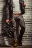 Stylish man with beard. In leather jacket holding a black leather bag, standing against brick wall, cropped Royalty Free Stock Photos