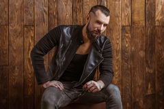 Stylish man with beard. In leather jacket holding sunglasses and looking at camera, sitting on a wooden background royalty free stock photo