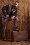 Stylish man with beard. In leather jacket leaning on a suitcase and looking at camera, standing on a wooden background royalty free stock photography