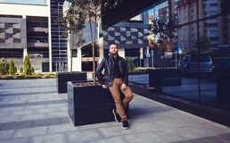 Man with a beard in a leather jacket. Stylish man with a beard in a leather jacket sits near a shopping center Royalty Free Stock Images