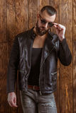 Stylish man with beard. In leather jacket and sunglasses, looking at camera, standing on a wooden background royalty free stock image