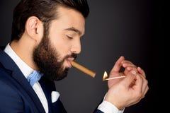Stylish man with beard lighting cigar Stock Photography