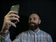 Stylish man with a beard and mustache makes selfie on the phone on a black background.  stock images