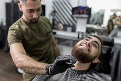 Stylish man with a beard sits at a barbershop. Barber trims mens beard with scissors. royalty free stock photos
