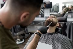 Stylish man with a beard sits at a barbershop. Barber trims mens beard with scissors. stock photo