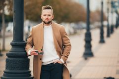 Stylish man with beard standing on street in brown coat with sunglasses in hand. Handsome young guy with modern hairstyle posing to camera. Concept lifefestyle stock images
