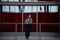 Stylish man with a beard on the terrace. Full length portrait of stylish mature man standing in beautiful big hall with glassy red color wall on background, male royalty free stock photo