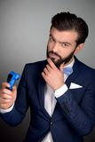 Stylish man with beard using electric shaver Royalty Free Stock Images