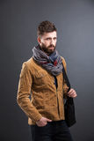 Stylish man with black leather bag. Portrait of bearded man with leather bag and stylish clothes looking at camera. Studio shot. Isolated Royalty Free Stock Photography