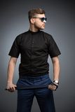 Stylish man in black shirt and mirrored sunglasses. Posing, playing with a tie. Studio shot Royalty Free Stock Photo