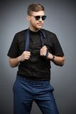 Stylish man in black shirt and mirrored sunglasses. Posing, playing with a tie. Studio shot Royalty Free Stock Image
