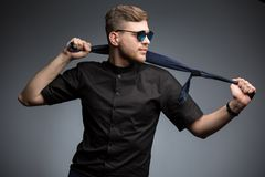 Stylish man in black shirt and mirrored sunglasses. Posing, playing with a tie. Studio shot Stock Photos