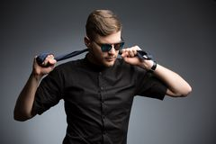 Stylish man in black shirt and mirrored sunglasses. Posing, playing with a tie. Studio shot Royalty Free Stock Images