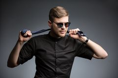 Stylish man in black shirt and mirrored sunglasses. Posing, playing with a tie. Studio shot Stock Image
