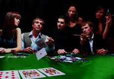 Stylish man in black suit folds two cards in casino poker at Las Vegas over black. Stock Photos