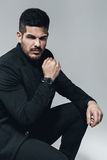 Stylish man in black with watch on hand Royalty Free Stock Image