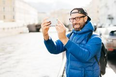 Stylish man with blue charming eyes and beard wearing blue anorak, eyewear and cap making selfie with mobile phone against big cit. Y background. Young tourist stock images
