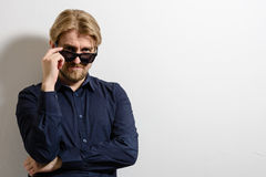 Stylish man in a blue shirt and sunglasses standing Stock Photos