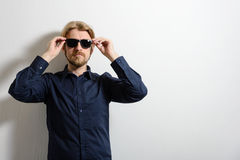 Stylish man in a blue shirt and sunglasses standing Royalty Free Stock Photo