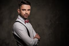 Stylish man with bow tie posing on dark background. Stock Photo