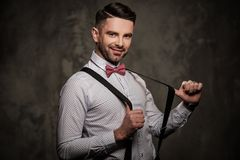 Stylish man with bow tie posing on dark background. Stock Photos