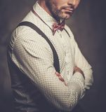 Stylish man with bow tie wearing suspenders and posing on dark  background. Stock Images