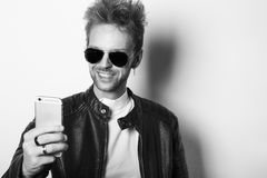 Stylish man checking his mobile phone. Stylish man with sunglasses andleather jacket checking his mobile phone Royalty Free Stock Photo