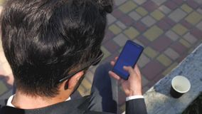 Stylish man in a classic suit and sunglasses sits and looks at the phone. view from above. businessman with telephone. 4k. 4k. Video stock footage