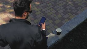 Stylish man in a classic suit and sunglasses sits in a park on a concrete bench and looks into the phone. businessman with. Telephone. 4k. 4k video stock video footage