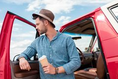 Stylish man with disposable cup of coffee standing at car during. Road trip royalty free stock photo
