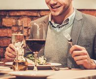 Stylish man eating at restaurant. Stock Image