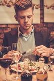 Stylish man eating at restaurant. Royalty Free Stock Image