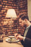 Stylish man eating at restaurant. Royalty Free Stock Images