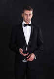 Stylish man in elegant black tuxedo with glass red wine Royalty Free Stock Photo