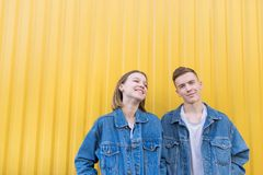 Man and girl are on a yellow background and smiling. Happy young hipsters. Portrait of a young couple against a yellow wall background. Stylish men and girl are royalty free stock photo