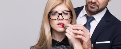 Stylish man hand helps apply red lipstick to blonde woman banner. Stylish men hand helps apply red lipstick to young blonde women banner royalty free stock images