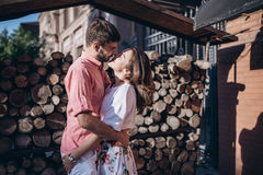 Stylish man and happy woman embrace in light on background of wooden firewood wall. Happy couple are hagging, romantic moment. Stylish men and happy women Stock Image
