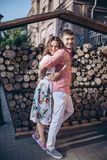 Stylish man and happy woman embrace in light on background of wooden firewood wall.  Happy couple are hagging, romantic moment Stock Images