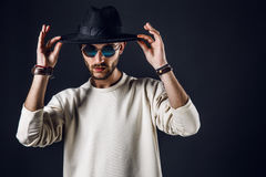 Stylish man in hat and sunglasses. Cool stylish handsome man wearing sunglasses holding hat. Horizontal studio shot Royalty Free Stock Images