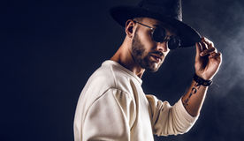 Stylish man in hat and sunglasses. Cool stylish handsome man wearing sunglasses holding hat. Horizontal studio shot Stock Images