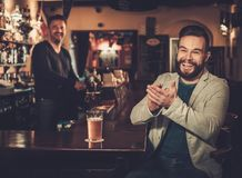 Stylish man having fun watching a football game on TV and drinking draft beer at bar counter in pub. Stock Photos
