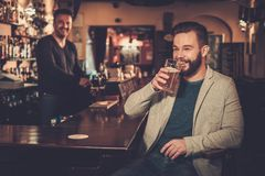 Stylish man having fun watching a football game on TV and drinking draft beer at bar counter in pub. Royalty Free Stock Photo