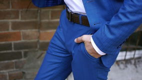 Stylish man in a jacket puts his hand in his trouser pocket stock video
