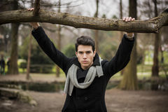 Stylish Man Leaning on Tree Branch Looking Afar Stock Photos
