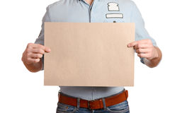 Stylish man in a light denim shirt and dark blue jeans is holding a blank sheet. Stylish man in a light denim shirt and dark blue jeans with a brown belt is Stock Images