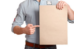 Stylish man in a light denim shirt indicates a blank sheet which holds a royalty free stock photos