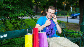 Stylish man on the phone at the park .  He trying a t-shirt Stock Images