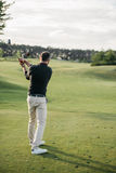 Stylish man playing golf on golf course at daytime. Back view of stylish man playing golf on golf course at daytime Royalty Free Stock Photography
