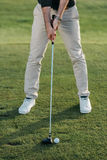 Stylish man playing golf on golf course at daytime. Cropped view of stylish man playing golf on golf course at daytime Stock Photos